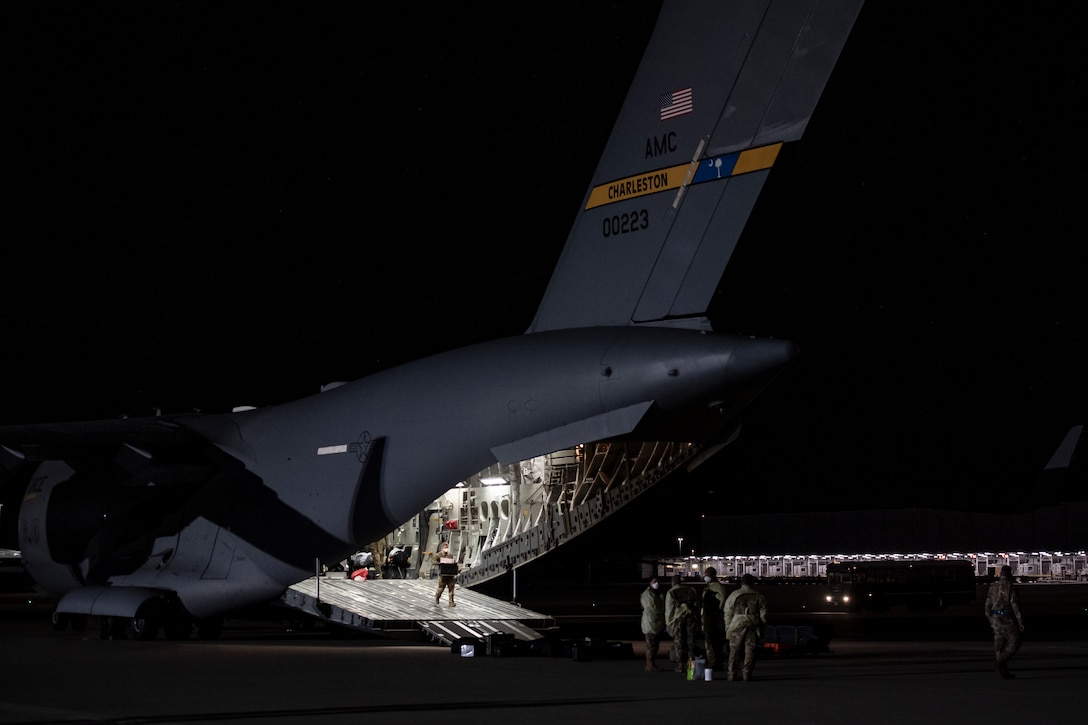 U.S. Air Force Airmen unload medical equipment after transporting COVID-19 patients during the first-ever operational use of the Transport Isolation System at Ramstein Air Base, Germany, April 10, 2020. The TIS is an infectious disease containment unit designed to minimize contamination risk to aircrew and medical attendants, while allowing in-flight medical care for patients afflicted by a disease--in this case, COVID-19. (U.S. Air Force photo by Staff Sgt. Devin Nothstine)