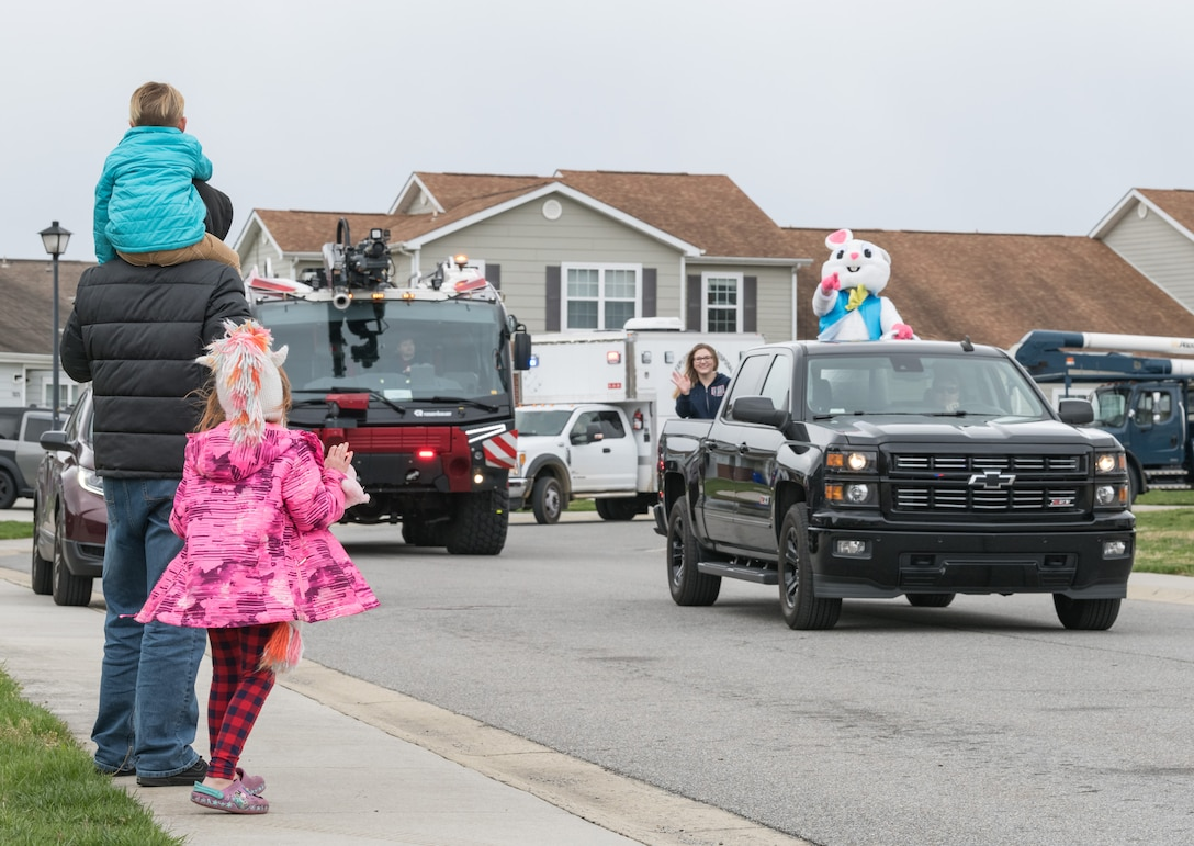 Staff Sgt. David Rhodes, 436th Logistics Readiness Squadron unit deployment manager, along with his son Keegan and daughter Hailey, wait for the Easter Bunny, Tech. Sgt. Jeffrey Seastrand, 436th LRS, to pass their home in Eagle Heights housing April 10, 2020, at Dover Air Force Base, Delaware. A small caravan of USO volunteers, 436th Security Forces Squadron and Civil Engineer Squadron vehicles, escorted the Easter Bunny around the housing area in a vehicle driven by Staff Sgt. Tate Booms, 436th LRS vehicle maintenance, accompanied by his wife Cassidy, USO Delaware volunteer. On this Good Friday, the Easter Bunny and residents observed social distancing to mitigate the spread of COVID-19. (U.S. Air Force photo by Roland Balik)