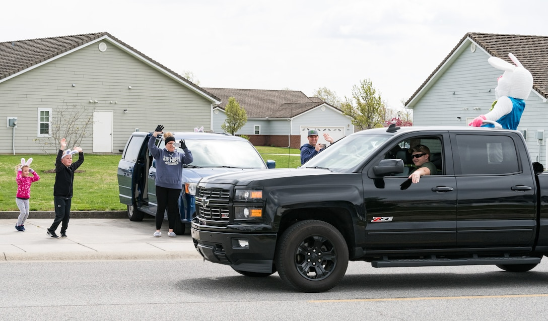 Tech. Sgt. David Miller, 436th Maintenance Group weapon systems controller, along with his family, wave to the Easter Bunny as he passes their vehicle in Eagle Heights housing April 10, 2020, at Dover Air Force Base, Delaware. A small caravan of USO volunteers, 436th Security Forces Squadron and Civil Engineer Squadron vehicles, escorted the Easter Bunny around the housing area in a vehicle driven by Staff Sgt. Tate Booms, 436th LRS vehicle maintenance, accompanied by his wife Cassidy, USO Delaware volunteer. On this Good Friday, the Easter Bunny and residents observed social distancing to mitigate the spread of COVID-19. (U.S. Air Force photo by Roland Balik)