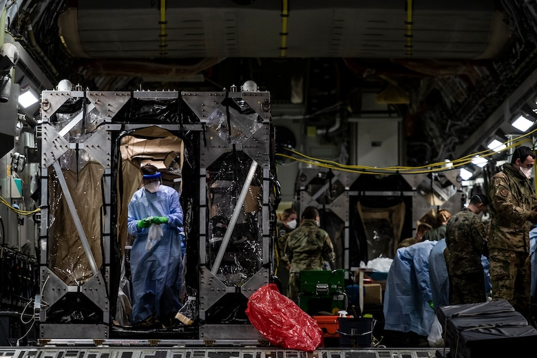 U.S. Air Force Airmen aboard a C-17 Globemaster III aircraft begin disinfecting and decontaminating the aircraft after the first-ever operational use of the Transport Isolation System at Ramstein Air Base, Germany, April 10, 2020. The TIS is an infectious disease containment unit designed to minimize contamination risk to aircrew and medical attendants, while allowing in-flight medical care for patients afflicted by a disease--in this case, COVID-19. (U.S. Air Force photo by Staff Sgt. Devin Nothstine)
