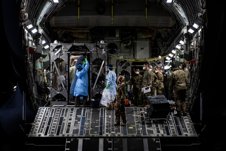 U.S. Air Force Airmen prepare to off-load COVID-19 patients during the first-ever operational use of the Transport Isolation System at Ramstein Air Base, Germany, April 10, 2020. The TIS is an infectious disease containment unit designed to minimize contamination risk to aircrew and medical attendants, while allowing in-flight medical care for patients afflicted by a disease--in this case, COVID-19. (U.S. Air Force photo by Staff Sgt. Devin Nothstine)
