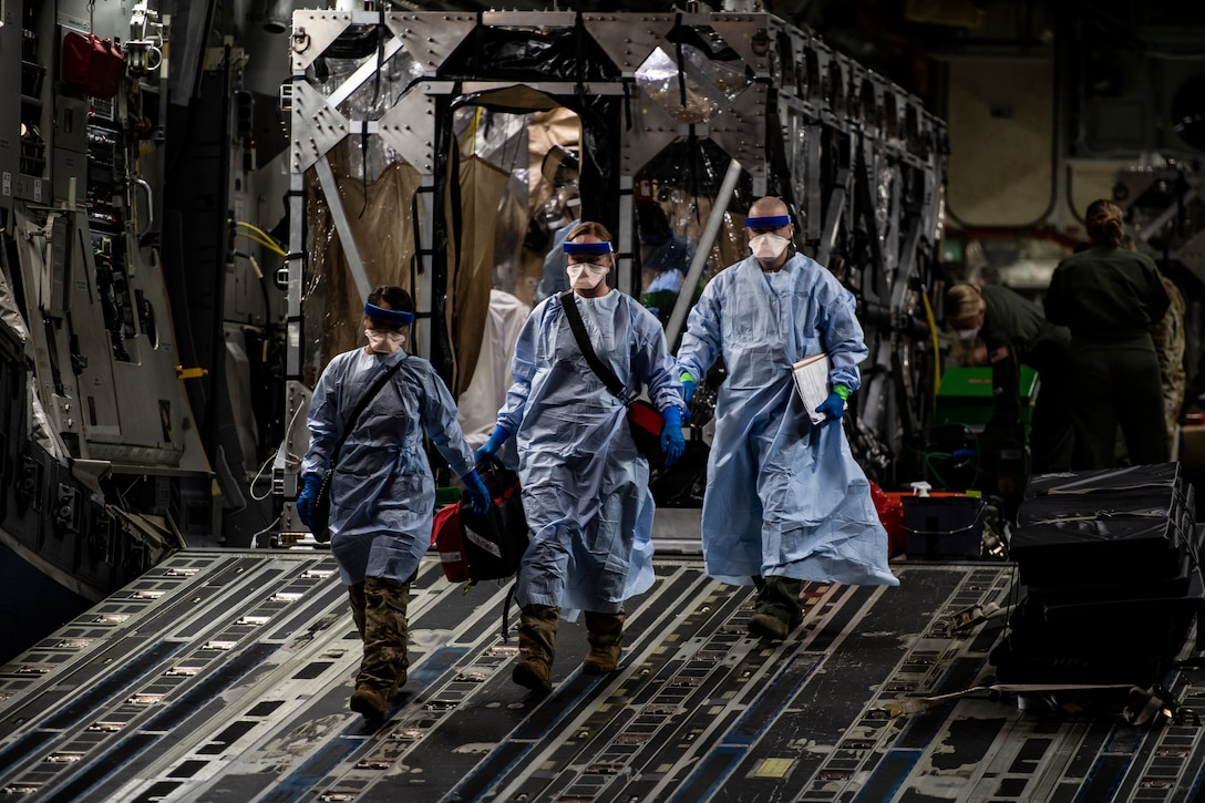 Three U.S. Air Force medical Airmen exit a C-17 Globemaster III aircraft following the first-ever operational use of the Transport Isolation System at Ramstein Air Base, Germany, April 10, 2020. The TIS is an infectious disease containment unit designed to minimize contamination risk to aircrew and medical attendants, while allowing in-flight medical care for patients afflicted by a disease. (U.S. Air Force photo by Staff Sgt. Devin Nothstine)