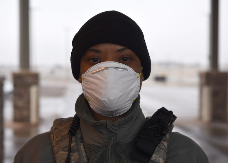 U.S. Air Force Airman 1st Class Laurente Drake, 460th Security Forces Squadron member, poses for a photo on April 2, 2020 at Buckley Air Force Base, Colo. Buckley AFB is currently in Health Protection Condition level Charlie in response to the spread of COVID-19 in the state of Colorado and to Members manning the gate are required to wear personal protective equipment and practice proper social distancing due to the risks associated with COVID-19. The HPCON Charlie defines base measures for a substantial disease threat and ensures Team Buckley is using the proper protocols and processes to prevent transmission. (U.S. Air Force photo by Airman 1st Class Haley N. Blevins)