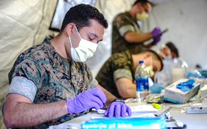 U.S. Navy Sailors with 2nd Medical Battalion, 2nd Marine Logistics Group pre-screen Marines with 2nd Light Armored Reconnaissance Battalion, 2nd Marine Division, on Marine Corps Air Station Cherry Point, North Carolina, March 30, 2020. II Marine Expeditionary Force is following the guidelines set by the Centers for Disease Control and Prevention and the Department of Health and Human Services to take the necessary precautions to protect redeploying service members and mitigate the spread of the coronavirus (COVID-19) outbreak. (U.S. Marine Corps photo by Lance Cpl. Scott Jenkins)