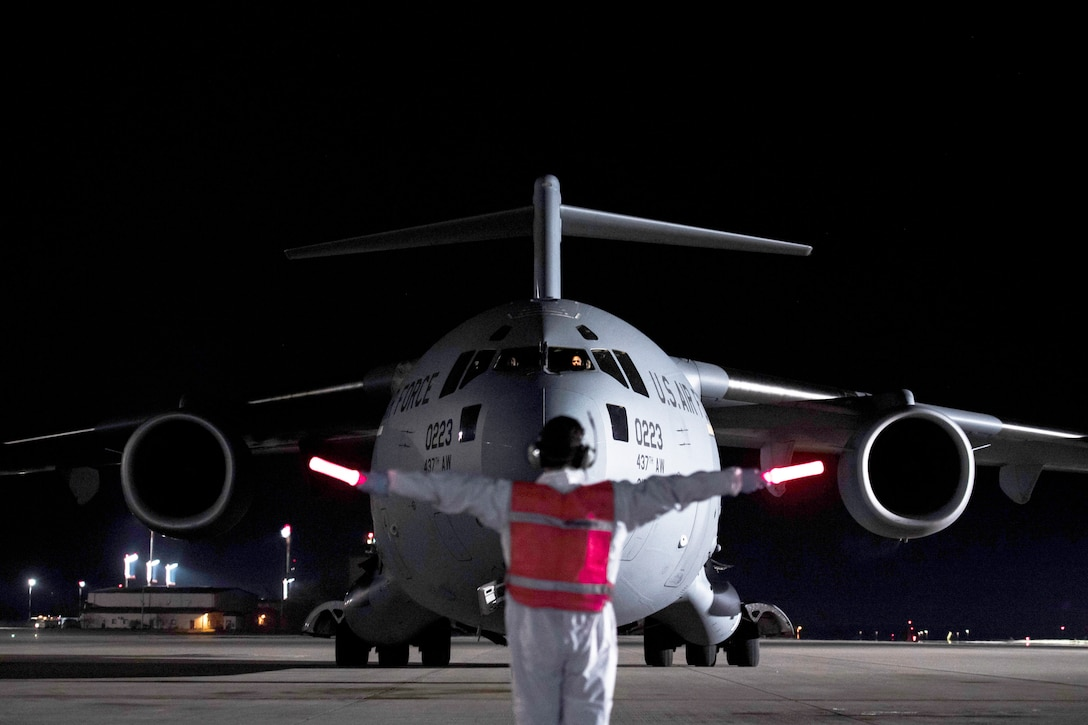 An airman holding out illuminated flashlights faces a large cargo jet as he guides it into position on a dark flight line.