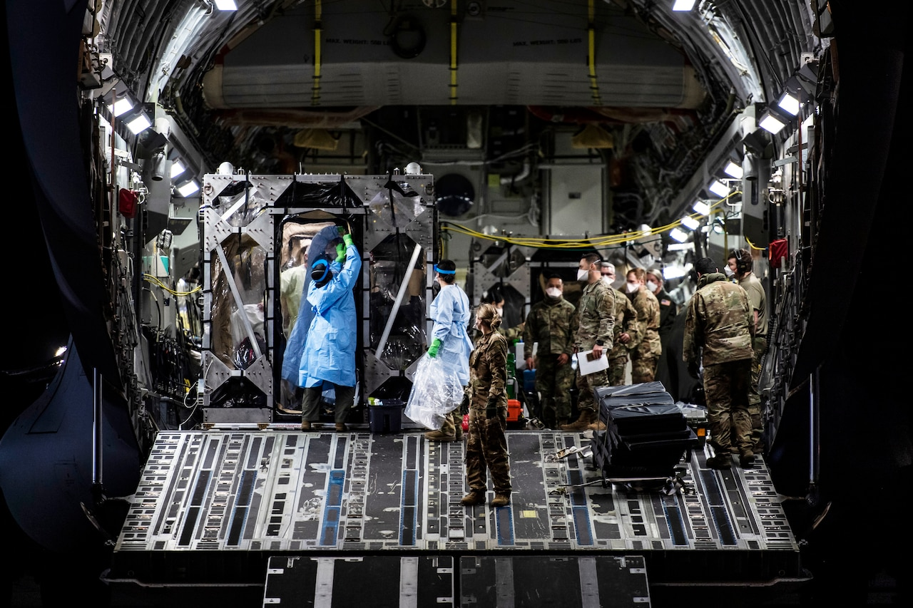 Airmen prepare to remove patients from an isolation chamber in the cargo bay of a large transport jet.