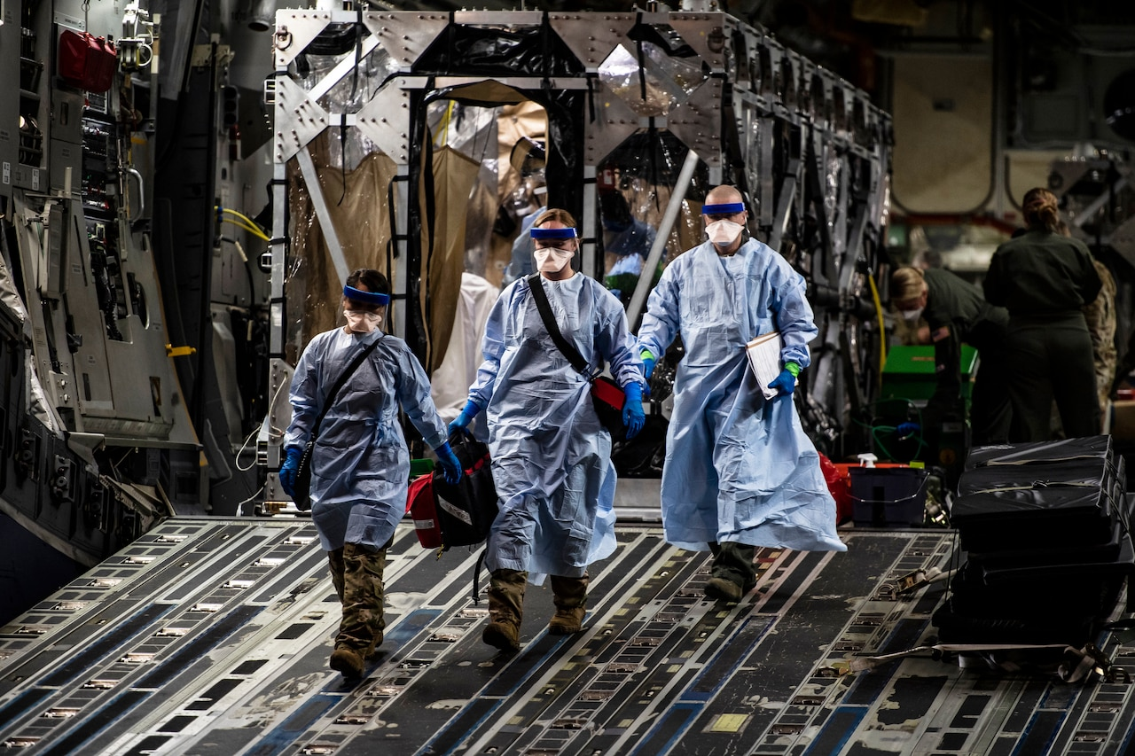 Airmen wearing personal protective gear walk down the open ramp of a large transport jet.