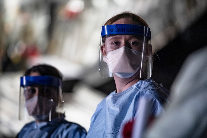 Airmen wearing personal protective gear wait for patient documentation in the cargo bay of a large transport jet.
