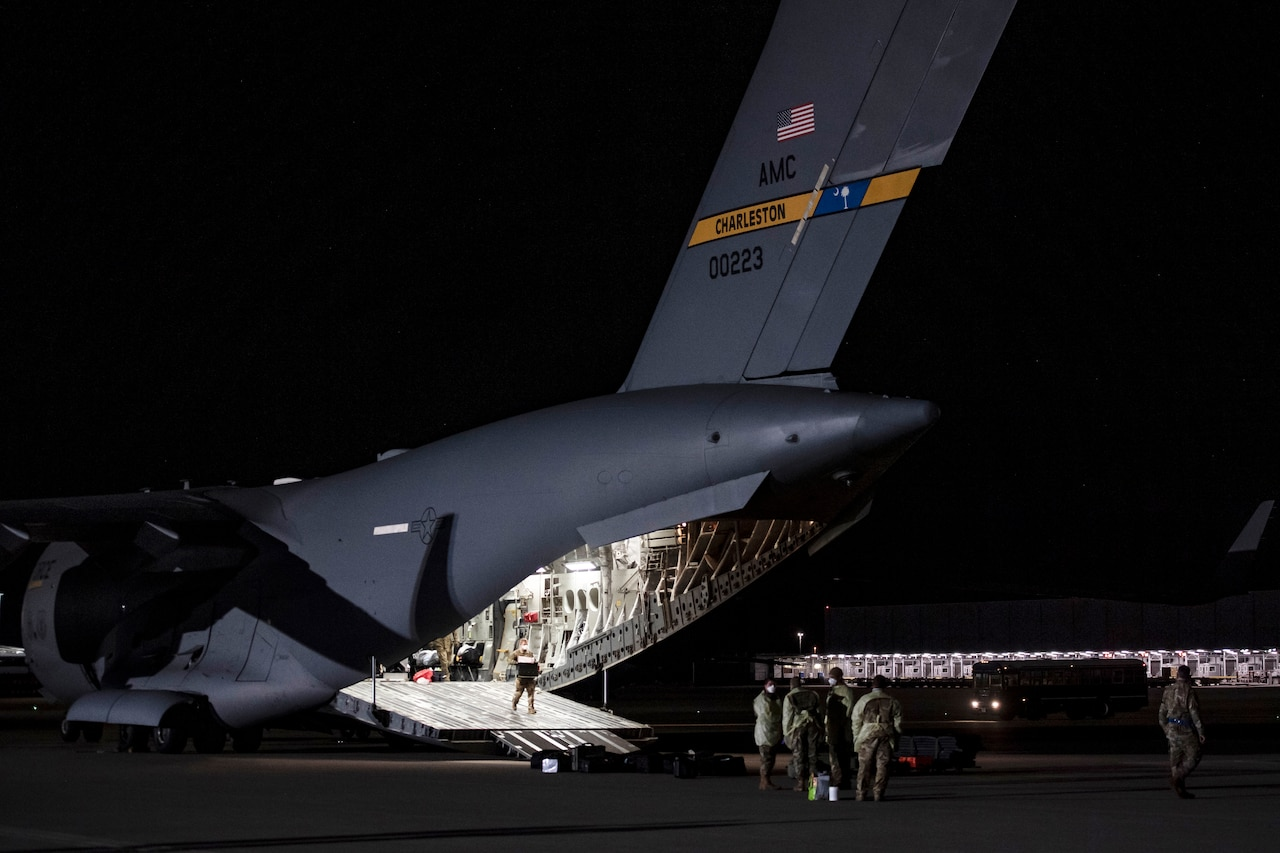 Airmen remove equipment from the brightly lit cargo bay of a large transport jet on a dark flight line.