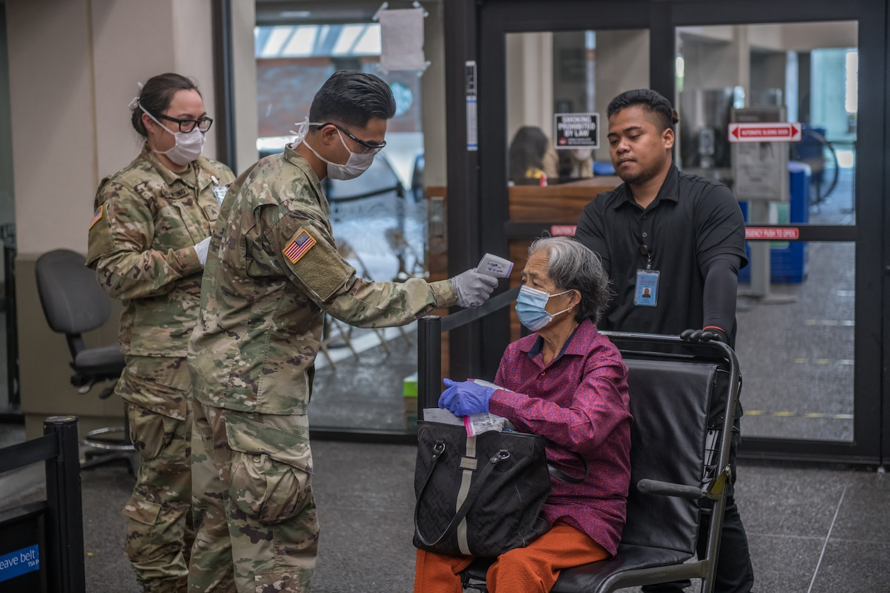 Soldier takes temperature of woman at airport.