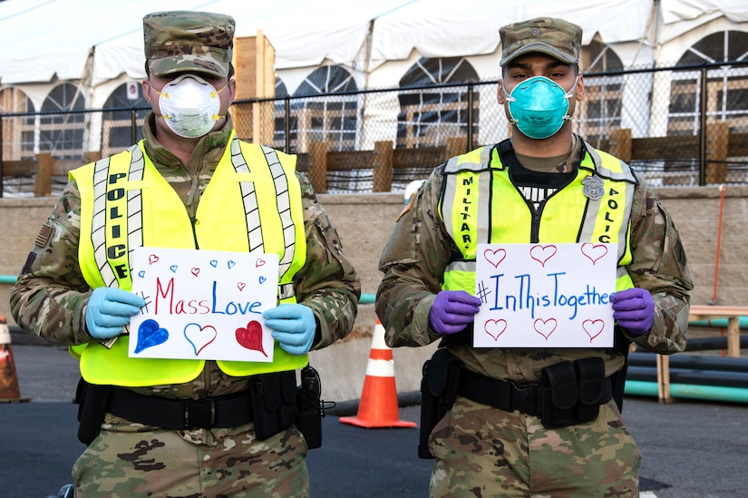 "Service members wearing face masks hold signs that read ""#MassLOve"" and ""#In This Together."""