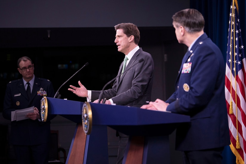 A civilian speaks at a lectern as an Air Force general stands beside him at an identical lectern.