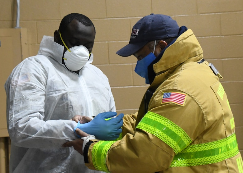 State Hazmat technicians help Soldiers from the 26th Maneuver Enhancement Brigade Headquarters and Headquarters Company and the 126th Aviation Battalion properly put on their Personal Protective Equipment before helping to administer COVID-19 tests to first responders at a drive thru testing facility, April 9, 2020, on the Big E fairgrounds in West Springfield, Massachusetts. The soldiers worked with other Massachusetts agencies getting individuals tested. The tested individuals should have their results digitally within 48 hours. (U.S. Air National Guard photo by Airman 1st Class Sara Kolinski)