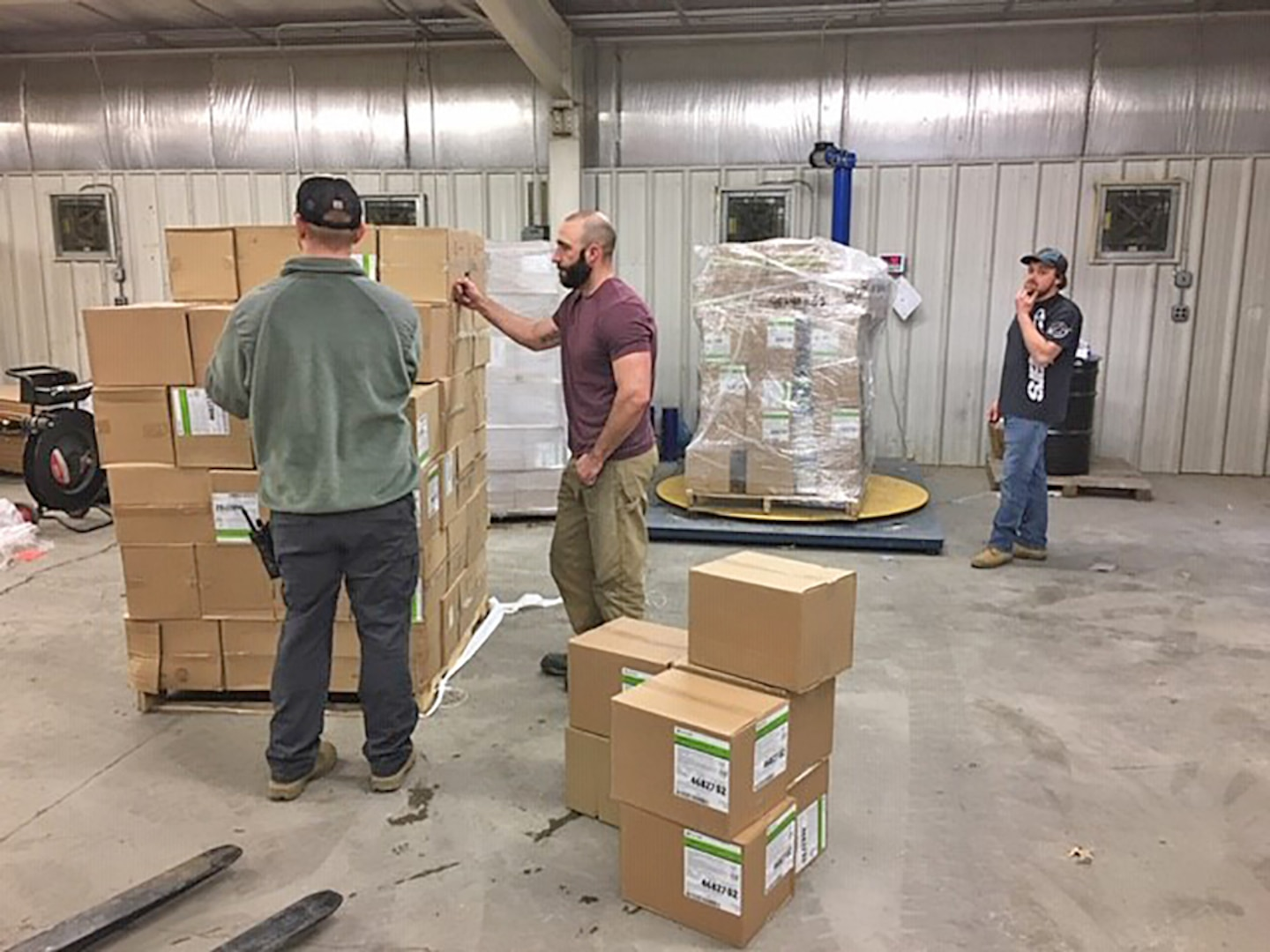Warehouse personnel prepare boxes of N95 masks for shipment to the Coast Guard.