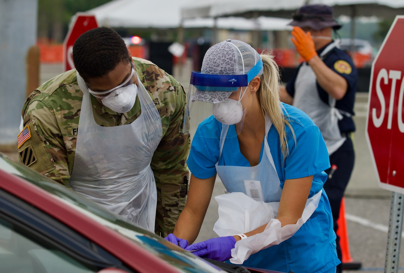 A Florida National Guard Soldier works alongside a nurse as he learns the processes at Jacksonville's COVID-19 community-based testing site at TIAA Bank Field, April 13, 2020. The FLNG's 3rd Battalion of the 20th Special Forces Group (Airborne) is taking over operation of the site.