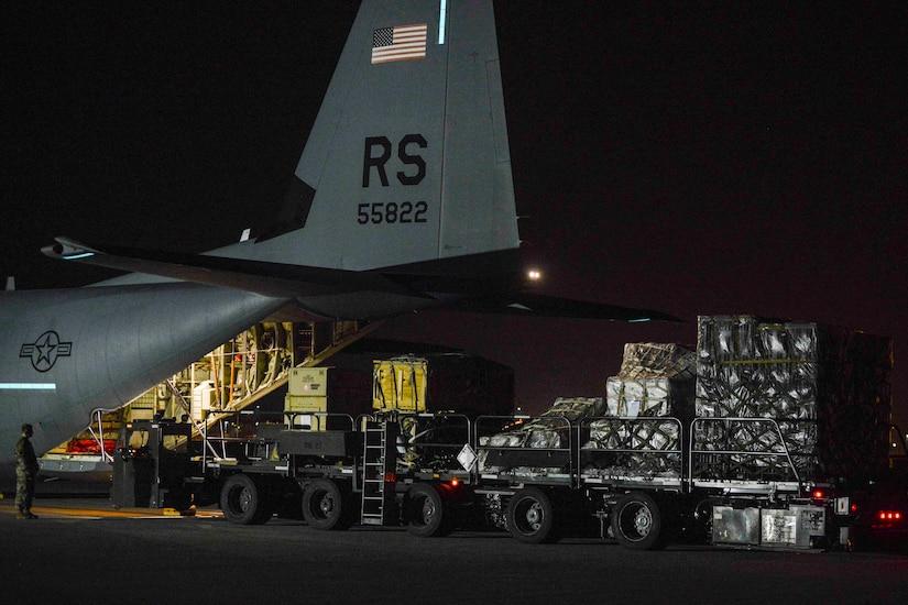 Airmen unload an aircraft at night.