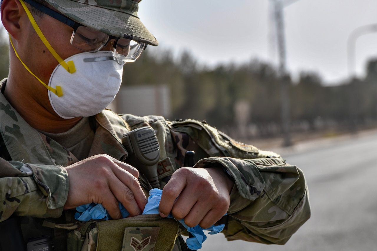An airmen wearing a facemask removes gloves from his supplies.