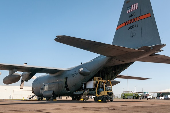 U.S. Air Force Airman 1st Class Evan Spotloe, foreground, a loadmaster, and Staff Sgt. Seth Johnson, a flight engineer, both with the 169th Airlift Squadron, Illinois Air National Guard, help load medical isolation pods into a C-130H Hercules in Eugene, Ore., April 8, 2020. Two 182nd Airlift Wing C-130 aircrews airlifted 250 isolation pods in a cross-country overnight homeland defense mission delivery to Chicago for use in an alternate medical facility.