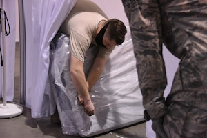 U.S. Air Force Staff Sgt. Devin Ralston from the 182nd Airlift Wing, based out of Peoria, Ill., places mattresses in treatment cubicles at an alternate care facility at the McCormick Place Convention Center in response to the COVID-19 pandemic in Chicago, April 11, 2020.