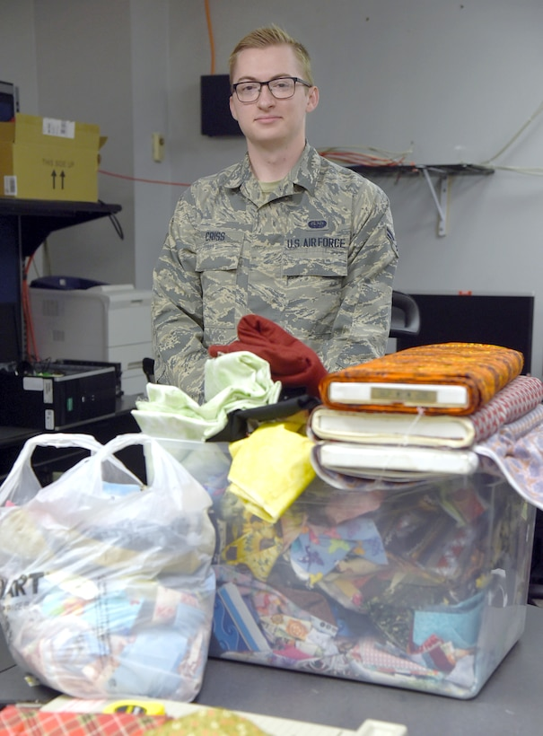 Airman First Class Stephen Criss stands next to a box of donated fabric and materials that he and other volunteers, both military and spouses, are making into face masks. 3-D printed clips for plastic face shields are also being made by volunteers. Several of each product have already been donated to local hospice organizations around the Tinker community, with many more in production to go to other medical facilities. (U.S. Air Force photo/Kelly White)