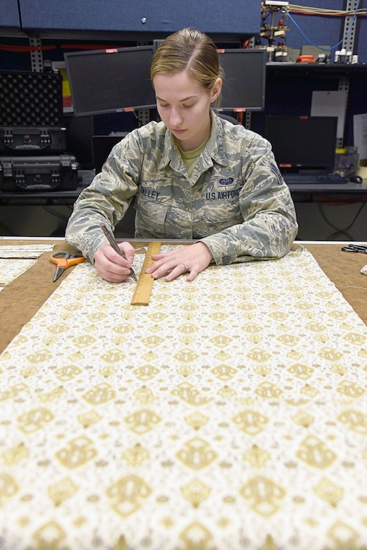 Airman First Class Sarah Talley, with the 552nd Air Control Network Squadron, measures fabric which will be made into face masks to be donated to local hospice and medical facilities around the Tinker community. Fabric and materials were donated by a local store, Sew and Sews, for this project. Over 100 fabric masks have already been made and are ready to donate. (U.S. Air Force photo/Kelly White)