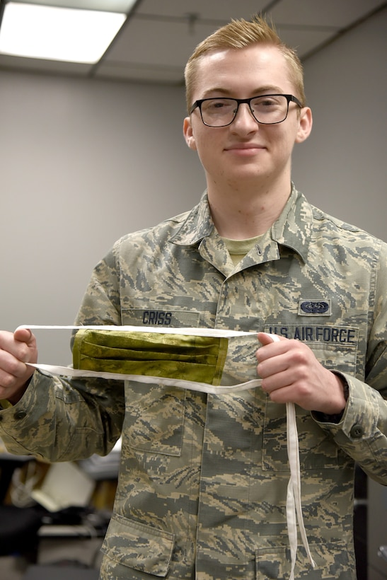 Airman First Class Stephen Criss, with the 552nd Air Control Network Squadron, shows one of the fabric masks that he and other military and spouse volunteers have been working on for the past two weeks. Fabric and materials were donated from a local store for the project. 3-D printed clips to hold plastic face shields are also being produced by volunteers. Both kinds of face protectors are being donated to local hospice and medical facilities in the community outside of Tinker. This project is the volunteers' way to giving back to the community that helps them so much. (U.S. Air Force photo/Kelly White)