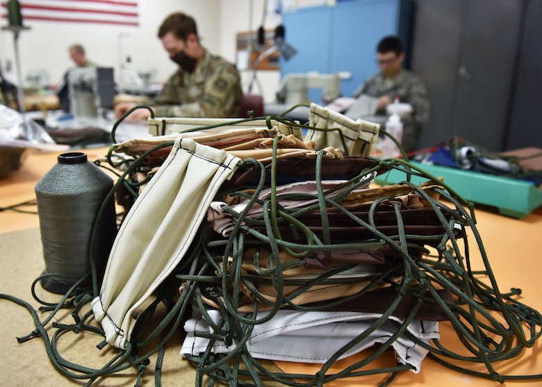 Finished Protective facemasks created by 92nd Operation Support Squadron Aircrew Flight Equipment Airmen rest on a table to be distributed at Fairchild Air Force Base, Washington, April 10, 2020. The mass mask production comes after the secretary of defense released a policy stating that all individuals including military personnel, civilian employees, family members and contractors on Department of Defense property, installations and facilities, must wear cloth face coverings where physical distancing measures are difficult to maintain. (U.S. Air Force photo by Senior Airman Lawrence Sena)