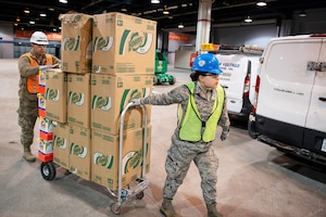 Two service members move a dolly loaded with boxes.
