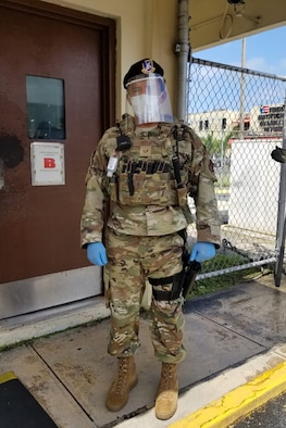 U.S. Air Force Staff Sgt. Alejandro Oyola with the 156th Security Forces Squadron checks identification at the entrance to Muñiz Air National Guard Base, Puerto Rico Air National Guard, while wearing personal protective equipment, April 9, 2020. The 156th SFS Defenders now have plastic face shields, created by 1st Lt. Jose Arroyo, a cyberspace operations officer with the 156th Communications Flight.