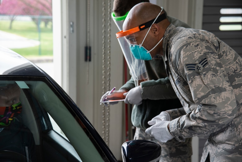 """Airman 1st Class Trent Ramsey, 436th Aerial Port Squadron air transportation cargo processor (left), and Senior Airman Dominique Hedges, 436th Medical Group physical therapy tech (right), man a medical screening check point while wearing 3D printed face shields April 10, 2020 at Dover Air Force Base, Delaware. The face shields were printed by the Dover Air Force Base Innovation Lab """"BEDROCK"""" for use by medical and security forces personnel supporting COVID-19 response efforts.  (U.S. Air Force photo by Airman 1st Class Jonathan Harding)"""