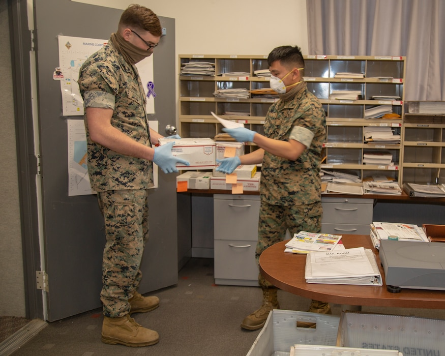 Corporal Colten Kokes, S-1 Administration clerk, and Lance Cpl. Zachary Gandiongco, Postal clerk, work together to process necessary mail using mandatory Personal Protective Equipment, such as latex gloves, a protective gaitor for the face or a protective mask, aboard Marine Corps Logistics Base Barstow, Calif., April 8. The new orders for Riverside County, San Bernardino County and MCLB Barstow, require the use of such PPE in public when obtaining necessities, and in circumstances when maintaining the safer six feet away for social distancing.