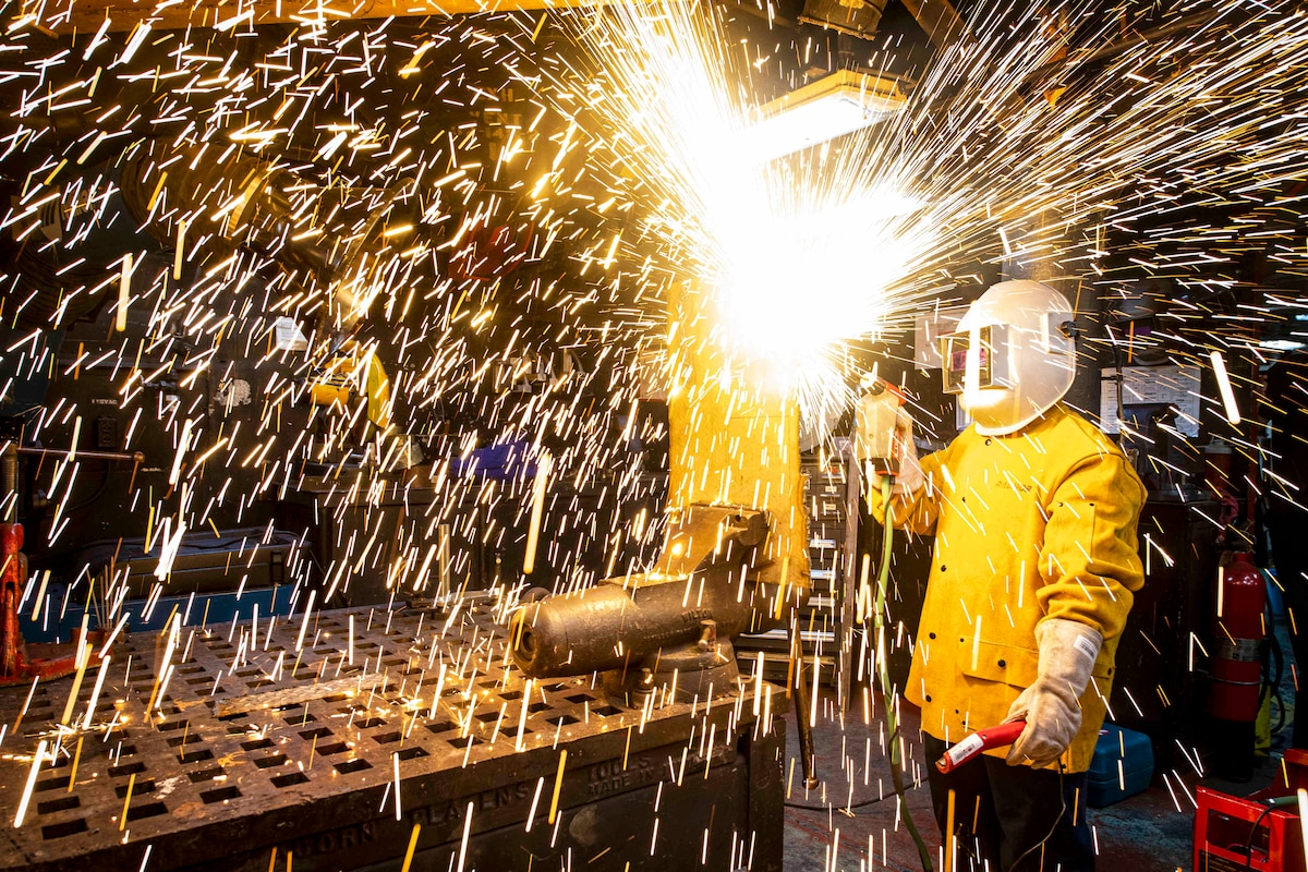Sparks fly in a room as a sailor in a helmet operates a cutting tool.