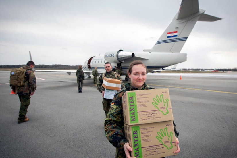 Service members carry boxes from an aircraft.