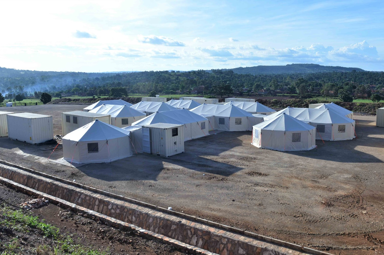 Several white tents and portable buildings in a large dirt field.