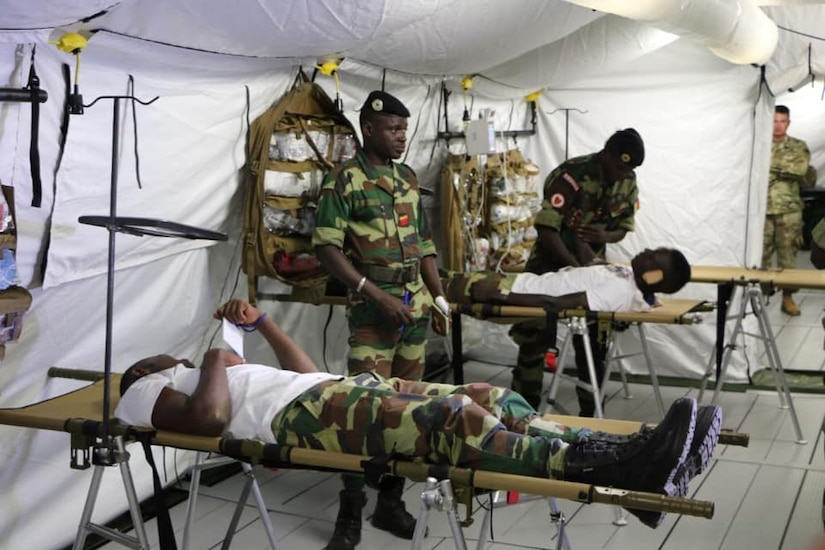 Two Senegalese soldiers stand as two others lie on cots during training for setting up a mobile hospital.