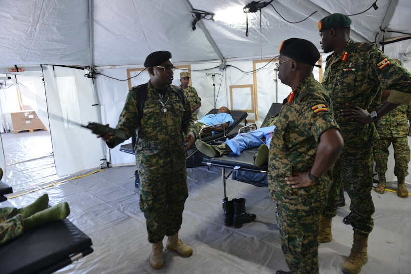 Ugandan officer briefs Ugandan soldiers on the layout of a mobile treatment facility.