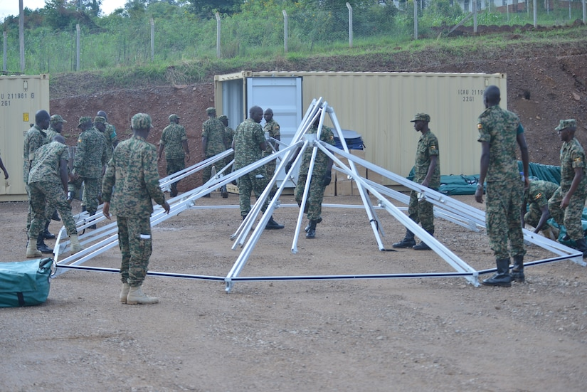 Ugandan soldiers surround a circular tent frame as they prepare to stand it up.