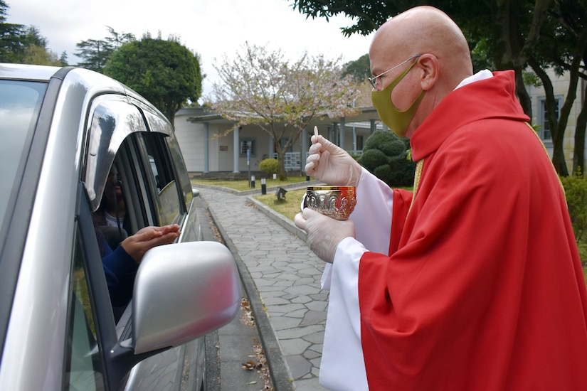A priest wearing gloves and a mask holds up a communion host as a parishioner inside a car prepares to receive it.