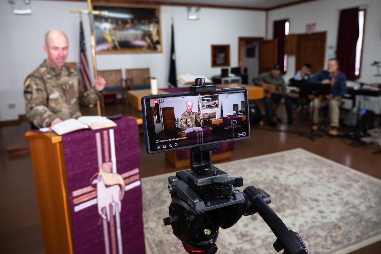 A smartphone in a tripod records a chaplain at a podium as a band sits in the background. A large cross is behind the chaplain.