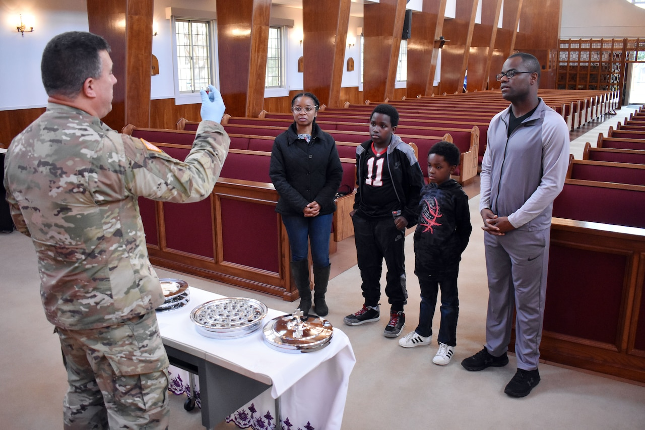 An Army chaplain holds up communion to a family of four at the front of an empty church.