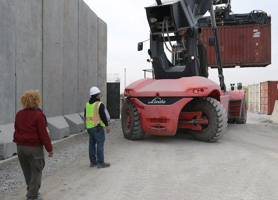 Tina Byrd, Afghanistan District Supply Specialist, guides the Safety Officer as the Big Lift removes an empty container from the USACE Afghanistan District supply yard in an effort to downsize excess storage units.