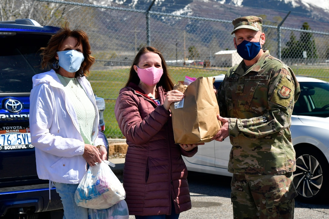 Joy Gingrich and Sarah Web, community volunteers, present Chief Master Sgt. Christopher Walker, 75th Air Base Wing Command Chief, with thousands of homemade face masks for the base military and civilian Airman personnel.