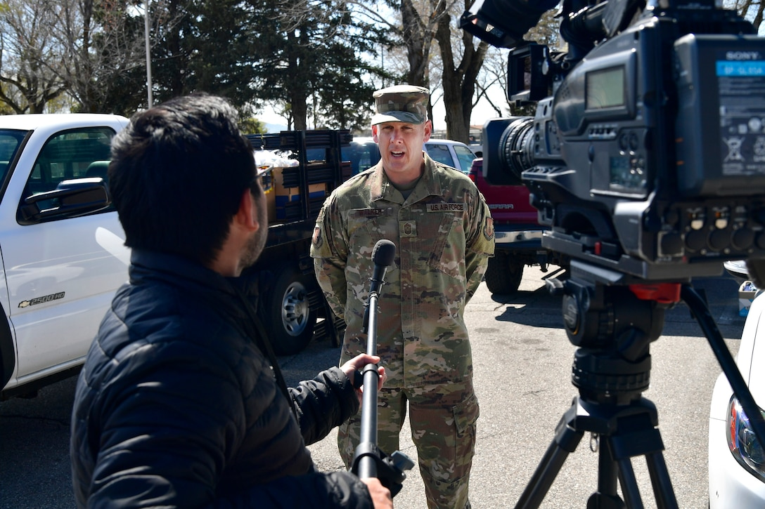 Chief Master Sgt. Christopher Walker, 75th Air Base Wing Command Chief, is interviewed by FOX 13 News, after being presented with thousands of donated face masks for the base military and civilian Airman personnel.