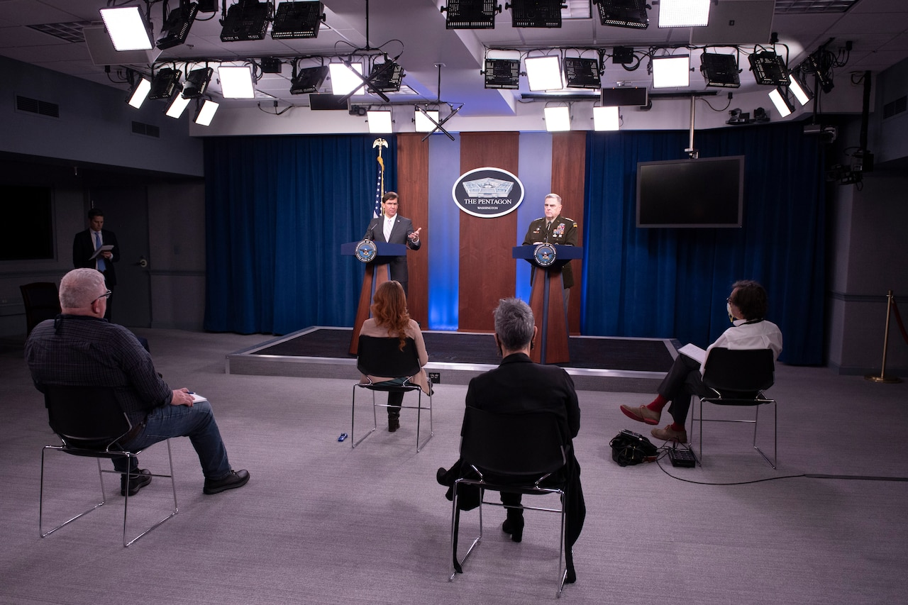 Defense Secretary Dr. Mark T. Esper and Army Gen. Mark A. Milley stand at lecterns in front of a few seated civilians.