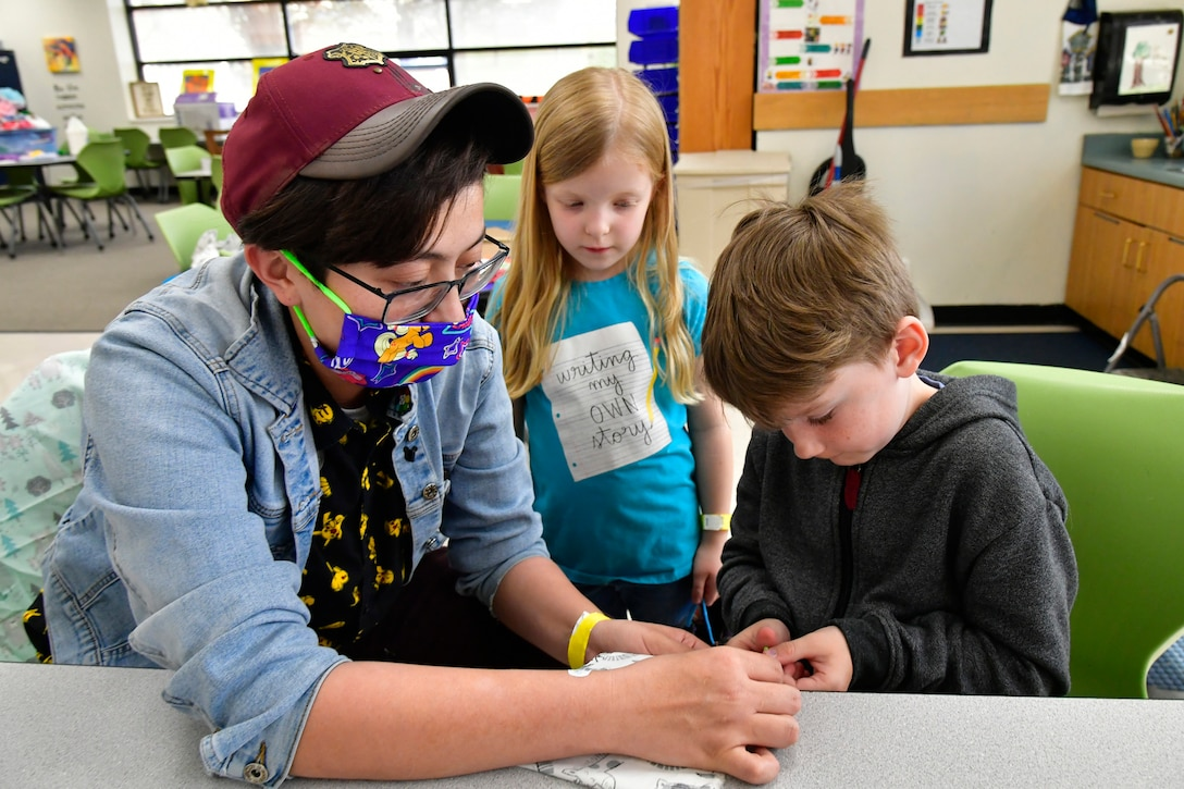 Kayla Hoffmann, left, Training and Curriculum Specialist, and Bethany Powell, center, watch as David Warren pins mask material to a pattern.