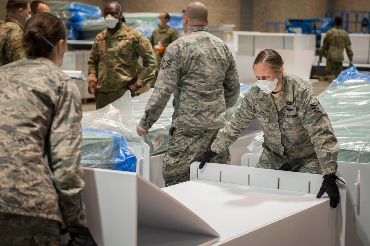 Service members work together to assemble equipment in a large indoor area.