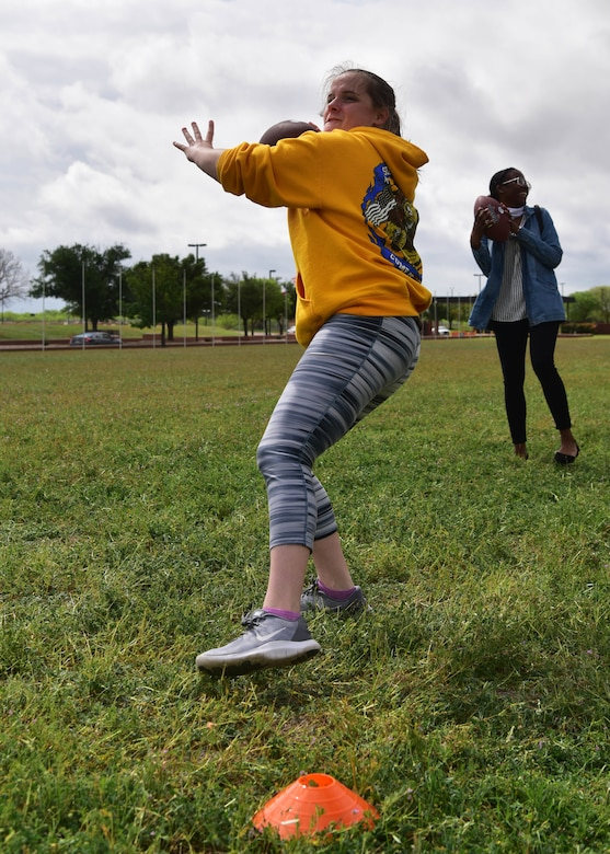A team of Airmen competes in the football punt, pass and kick portion of the 'Break the Pandemic' Morale event on Goodfellow Air Force Base, Texas, April 11, 2020. The 315th Training Squadron hosted the event, in which teams competed in eight different physical and mental challenges in order to escape the monotony of social distancing regulations in response to the COVID-19 pandemic. (U.S. Air Force photo by Staff Sgt. Chad Warren)