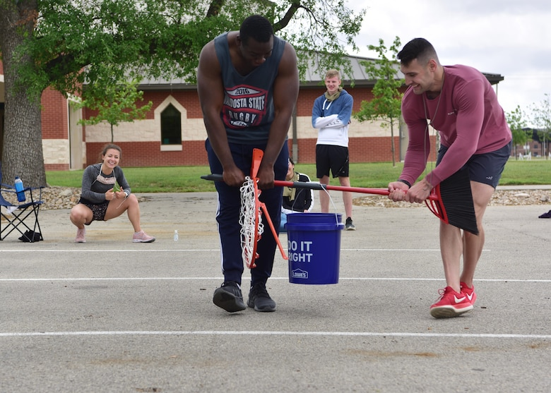 A team of 315th Training Squadron students competes in the water bucket challenge portion of the 'Break the Pandemic' Morale event on Goodfellow Air Force Base, Texas, April 11, 2020. The event consisted of a variety of items the team had to use to move a full water bucket while maintaining proper social distancing. (U.S. Air Force photo by Staff Sgt. Chad Warren)