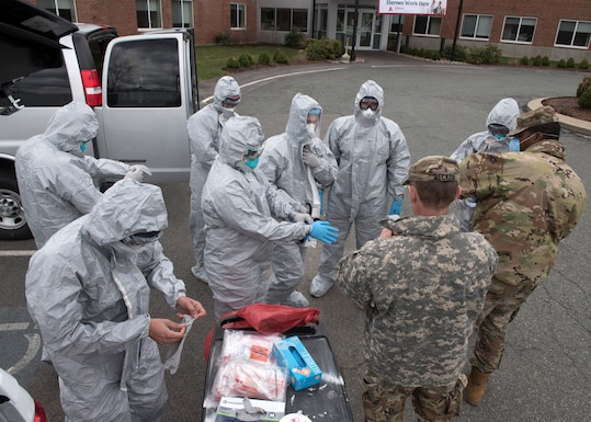 Soldiers and Airmen from the Massachusetts National Guard don proper personal protective equipment (PPE)