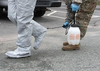 Soldiers and Airmen from the Massachusetts National Guard go through a detailed decontamination process and remove their personal protective equipment (PPE)